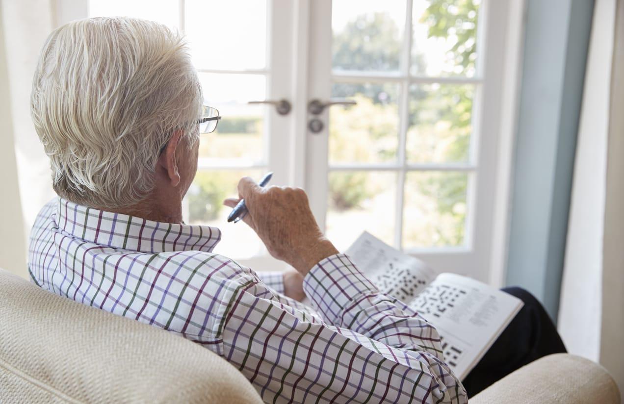 older man sitting with crossword